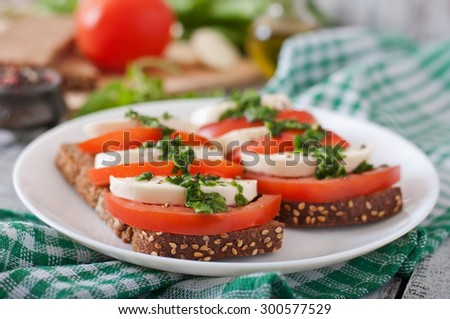 Useful dietary sandwiches with mozzarella, tomatoes and rye bread - stock photo