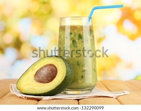 Useful fresh avocado and half avocado on wooden table on natural background - stock photo