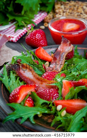Useful strawberry salad with arugula, nuts and bacon, berry sauce - stock photo