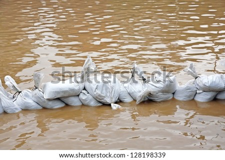 useless wall of sandbags to fend off raging river - stock photo