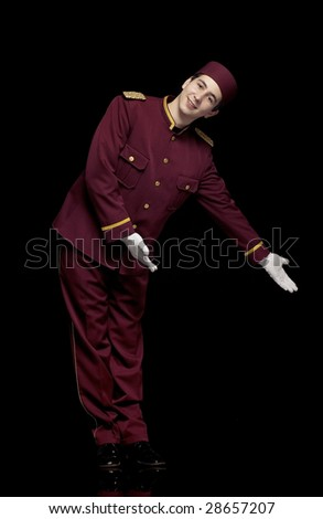 Usher with red uniform and white gloves points at presentation - stock photo