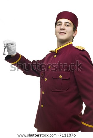 Usher with red uniform and white gloves presents a key - stock photo