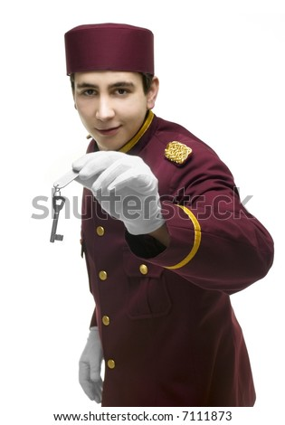 Usher with red uniform and white gloves presents a key including a label with one hand. FOCUS on hand and key. - stock photo