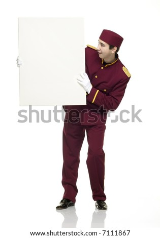 Usher with red uniform holds up a white panel. - stock photo