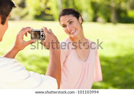 Using a camera, the man takes a photo of his friend smiling in the park