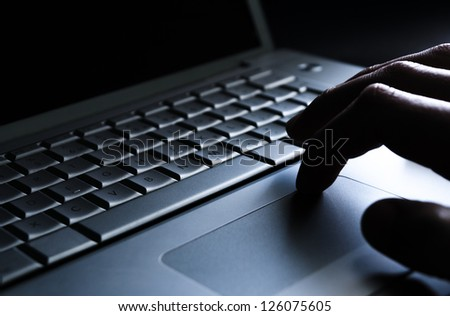 Using a laptop, finger on touchpad. Blue, cold tone./Laptop work - stock photo