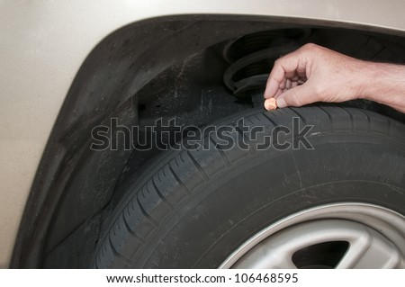 Using a Lincoln head penny to measure tire tread depth for safety Lincolns head is completely exposed indicating that this tire is no longer safe and needs replace - stock photo