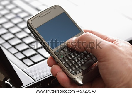 Using a PDA mobile phone with laptop keyboard background, blank screen for copy in high key - stock photo