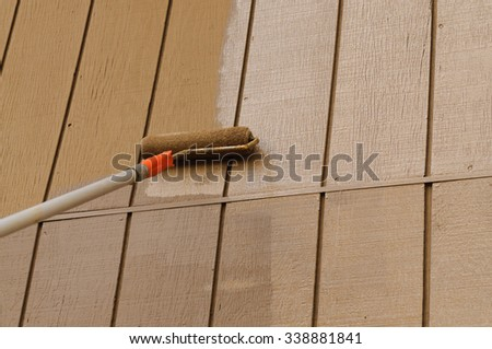 Using a roller applicator on an extension arm to paint the siding of a house - stock photo