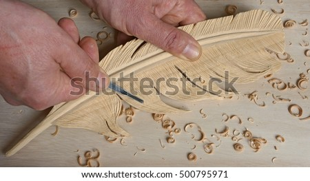 using a small gouge to add details on a feather carving