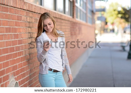 Using a smartphone. Girl standing next to a brick wall while using a cell phone. - stock photo