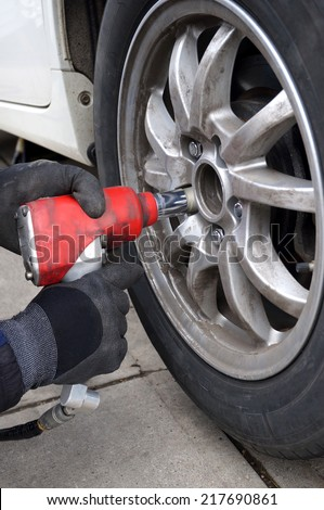 Using an air impact wrench to change tires. - stock photo