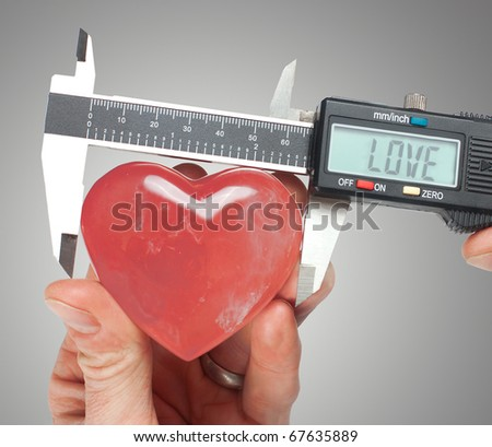 Using calipers to exactly measure a crystal heart - stock photo