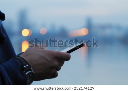 Using cellphone with defocused city lights and river reflection. - stock photo
