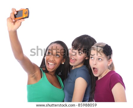 Using digital compact camera taking fun self portrait photograph for three pretty young teenager girl friends a blonde caucasian, an oriental Japanese and an African American mixed race student. - stock photo