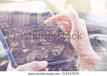 Using digital tablet double exposure and and cityscape background. Business & technology concept.