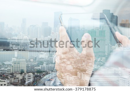 Using digital tablet double exposure and and cityscape background. Business technology concept.  - stock photo