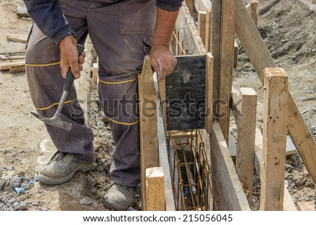 Using hammer and preparing form for concrete with reinforcing rods. Selective focus. - stock photo
