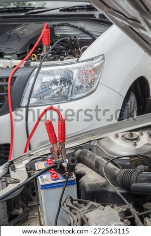 Using jumper cables to charge a dead car battery from  another vehicle in raining day. - stock photo