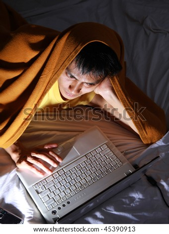 using laptop on bed - stock photo