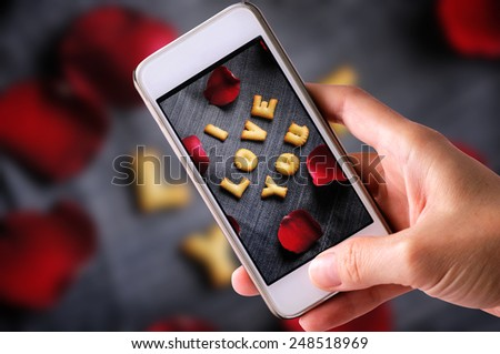 using mobile phone to take photos of Cookies ABC in the form of word I LOVE YOU alphabet  with red rose petal on old jean background, Valentines day - stock photo