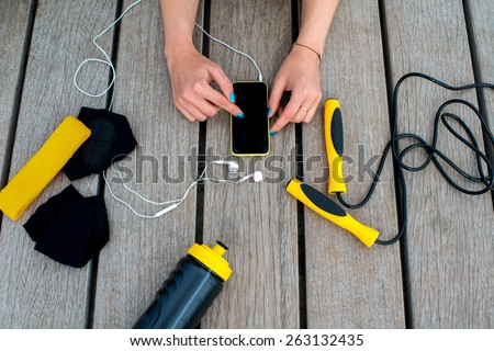 Using mobile phone with empty screen on the wooden desk surrounded with sport equipment. Sport mobile application concept - stock photo