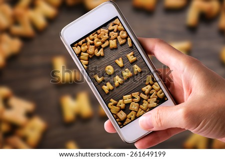 using mobile phones to take photos of Cookies ABC in the form of word LOVE MAMA alphabet on old wood background, Valentines day - stock photo