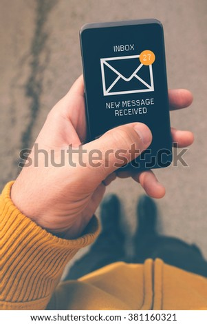 Using mobile smartphone to access e-mail inbox, man viewing incoming messages while walking on street, top view, selective focus, retro tone filtered image. - stock photo
