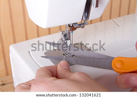 Using scicssors to cut thread on sewing machine hands showing - stock photo