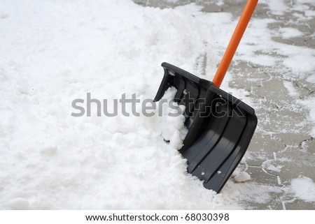 Using snow shovel on a backyard - stock photo