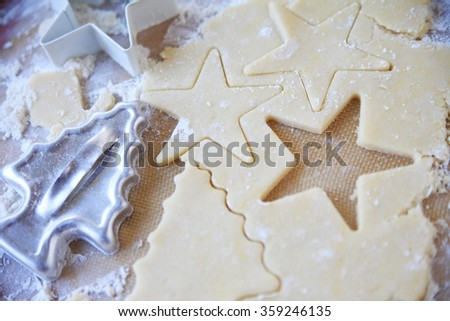 Using star and tree cookie cutters on sugar cookie dough - stock photo