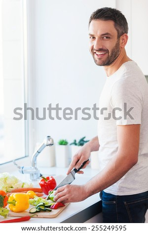 Using the best veggies for my salad. Handsome young man cutting vegetables and smiling while standing in the kitchen  - stock photo