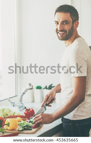 Using the freshest veggies for salad. Handsome young man cutting vegetables and smiling while standing in the kitchen - stock photo