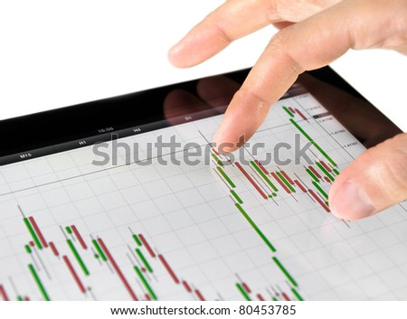 Using touch screen tablet for analyzing stock market chart. - stock photo