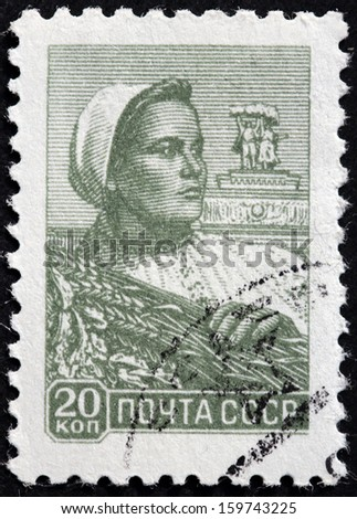 USSR - CIRCA 1958: A stamp printed by USSR (Russia) shows a woman farm worker holding a wheat bundle, circa 1958. - stock photo
