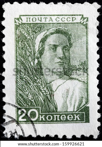 USSR - CIRCA 1948: A stamp printed by USSR (Russia) shows a woman farm worker holding a wheat bundle, circa 1948. - stock photo