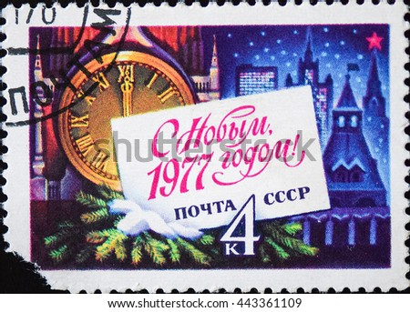 USSR - CIRCA 1976: A stamp printed in USSR shows Kremlin tower with red star, red USSR flag, fir-tree, snow for New Year 1977, series, circa 1976 - stock photo