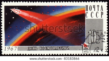 USSR - CIRCA 1967 A stamp printed in USSR shows rocket on Earth orbit, devoted to Cosmonauts Day, circa 1967 - stock photo