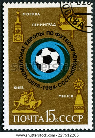 """USSR - CIRCA 1984: A stamp printed in USSR, shows Soccer ball and emblems of cities, series """"European Youth Soccer Championship """", circa 1984 - stock photo"""