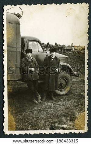USSR - CIRCA 1954 : An antique photo shows Two men stand near a truck, 1954
