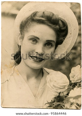 USSR - CIRCA 1947: Portrait of a young beautiful woman with white roses, circa 1947 - stock photo