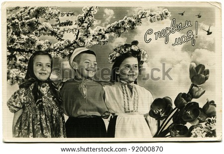 USSR  - CIRCA 1960: Postcard printed in the USSR honoring 1st of May shows two girls and a boy on the background of a flowering garden, circa 1960. Text in Russian: May 1. Happy Holidays! - stock photo