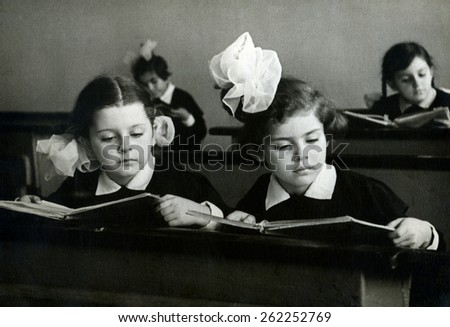 Ussr - CIRCA 1963s: An antique Black & White photo of Portrait of girls reading book in classroom - stock photo