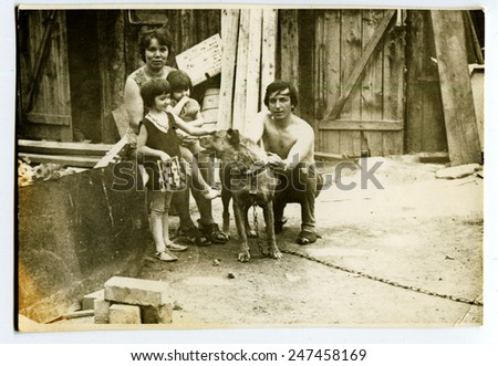 Ussr - CIRCA 1970s: An antique Black & White photo show family in the yard with the dog