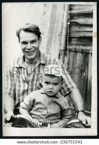 Ussr - CIRCA 1970s: An antique Black & White photo show happy father carries his son on a bicycle
