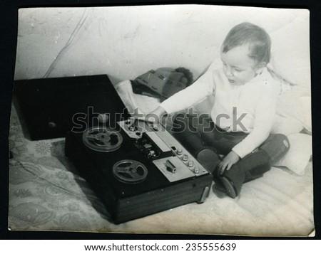 Ussr - CIRCA 1980s: An antique Black & White photo show little boy sitting near the tape - stock photo