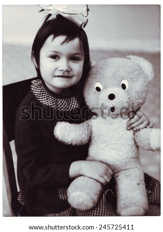 USSR - CIRCA 1970s: An antique photo shows little girl hugging a Teddy bear. Photo made in kindergarten CIRCA 1970s