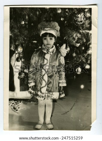 USSR - CIRCA 1980s: An antique photo shows little girl near Christmas tree, circa 1980s - stock photo