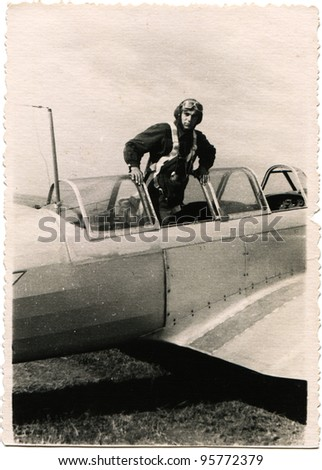 USSR - CIRCA 1950s: pilot in a helmet standing in front of the cockpit of military aircraft, circa 1950s - stock photo