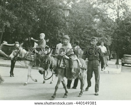 USSR - CIRCA 1970s: Retro photo shows children ride on donkeys in the park. Vintage black & white photography.